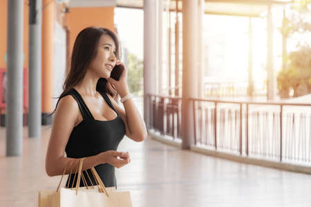 Beautiful young asian woman is carrying shopping bags with shopping bags enjoying in shopping and using a smart phone while doing shopping in the outlet, shopping mall.