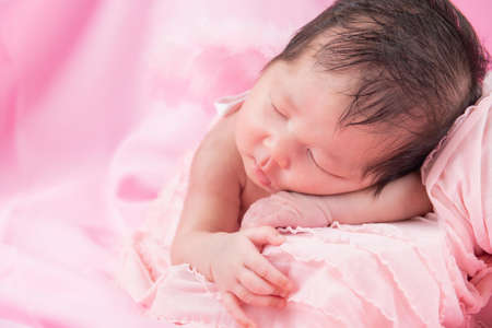 Portrait of a one month old sleeping, newborn baby girl on a pink blanket. Concept portrait studio fashion newborn.