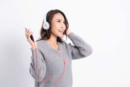 Young beautiful woman wearing a gray sweater is lying and listening to music wearing white music headphones isolated on white background. She is relaxing and happiness Zdjęcie Seryjne