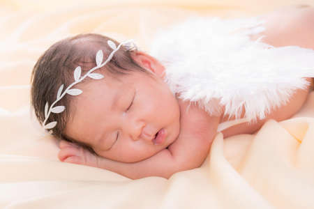 Portrait of a one month old sleeping, newborn baby girl. She is wearing a white crown headband, angel wings and sleeping on a cream blanket. Concept portrait studio fashion newborn.