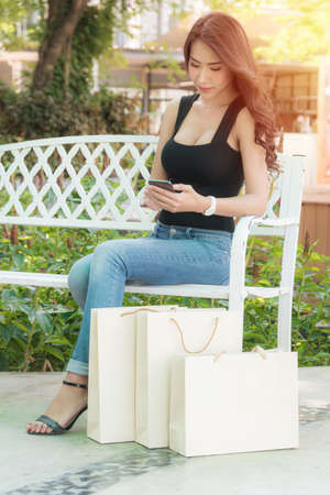 Beautiful woman wearing a black shirt and jeans perfect body shape, is sitting in a chair with a shopping bag at outdoor shopping mall in the evening when the red light shines.