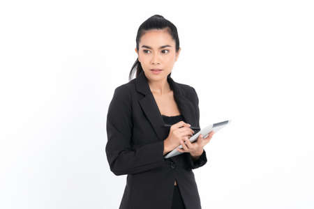 Portrait business woman using tablet digital device wearing a black suit at studio shot isolated on white background. Pretty female model. Confident professional office worker.