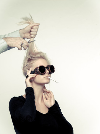 Steampunk inspired image of young woman with sunglasses not paying attention to a hairdressers hand is cutting off her hair