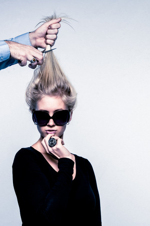 Fashion image of young woman with sunglasses not paying attention to a hairdressers hand is cutting off her hair photo