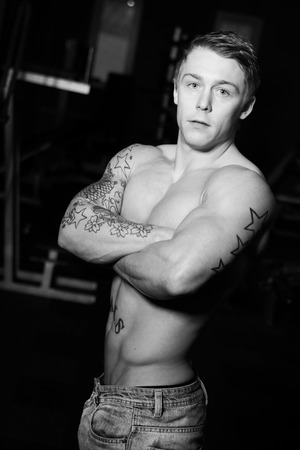 b w: Young bodybuilder posing wearing jeans