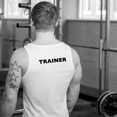 fitnesscenter: personal trainer in gym facing away Stock Photo
