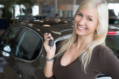 Smiling woman holding car key in dealership photo