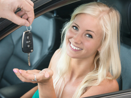 Smiling young woman receiving key to new car