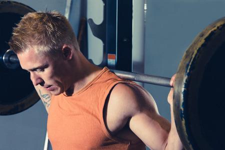 fitnesscenter: Young bodybuilder in smith machine