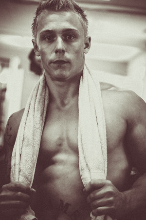 Young bodybuilder standing with towel around his neck Stock Photo