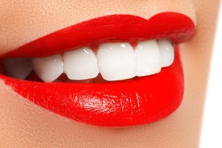 dientes sanos: Primer plano sonrisa femenina feliz con los dientes sanos y blancos, brillantes labios rojos de maquillaje. Cosmetología, odontología y cuidado de la belleza. Macro de la boca sonriente de la mujer