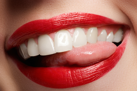 Close-up happy female smile with healthy white teeth, bright red lips make-up. Cosmetology, dentistry and beauty care. Macro of woman's smiling mouth Stockfoto