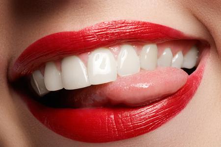 Close-up glücklich weibliche Lächeln mit gesunden weißen Zähnen, leuchtend roten Lippen Make-up. Kosmetologie, Zahnmedizin und Schönheitspflege. Makro von lächelnden Mund der Frau