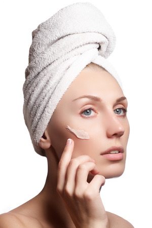 moisturize: Beautiful face of young woman with cosmetic cream on a cheek. Skin care concept. Closeup portrait isolated on white. Close-up young beautiful face of girl applying moisturize cream