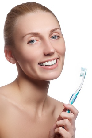 orthodontist: Beautiful woman with toothbrush. Dental care background. Closeup on young woman showing toothbrush. Beautiful young woman holding a toothbrush in hand Stock Photo