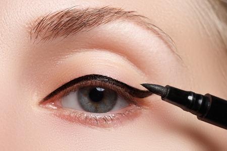 Beautiful model applying eyeliner close-up on eye Stockfoto