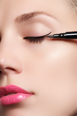 Beautiful model applying eyeliner close-up on eye Foto de archivo