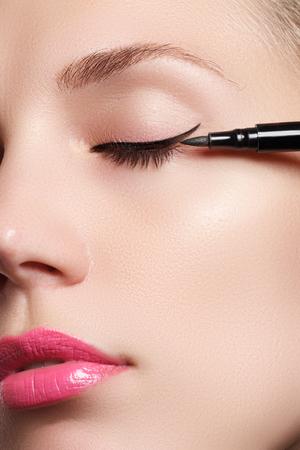 Beautiful model applying eyeliner close-up on eye Standard-Bild