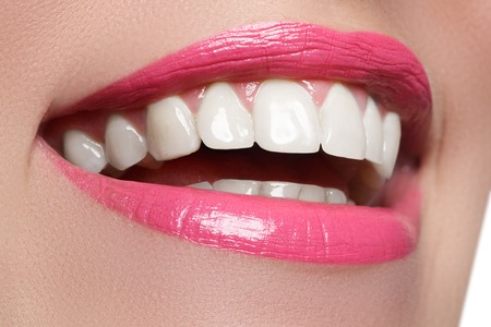 Macro happy womans smile with healthy white teeth, bright pink .lips make-up. Stomatology and beauty care. Woman smiling with great teeth. Cheerful female smile with fresh clear skin Stock Photo