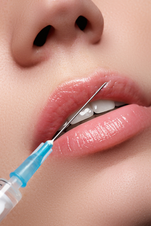 Close-up of beautiful woman gets injection in her lips. Full lips. Beauty concept Banco de Imagens