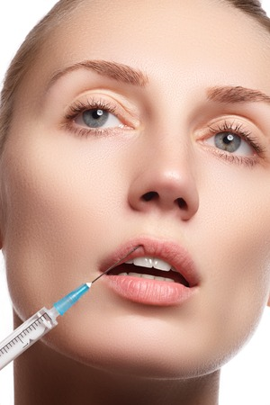 augmentation: Portrait of young woman getting cosmetic injection. Close-up of beautiful woman gets injection in her face. Filler injections. Lip augmentation. Beautiful perfect lips