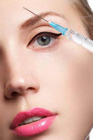 dermal: Beautiful woman gets beauty facial injections. Face aging injection. Aesthetic Cosmetology Stock Photo