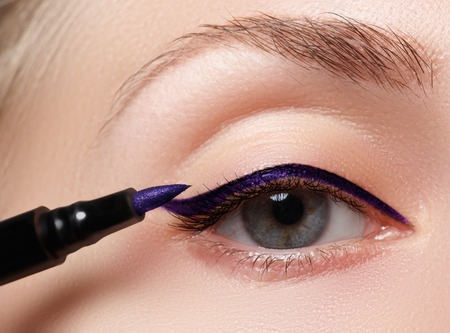 Woman make-up applying close-up. Eyeliner. Cosmetic eyeshadows. Eyeline brush for make-up. Beauty girl with perfect skin. Eyelashes. Blue eyes. Makeover