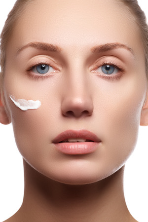 moisturize: Beautiful face of young woman with cosmetic cream on a cheek. Skin care concept. Closeup portrait isolated on white. Close-up young beautiful face of girl applying moisturize cream.
