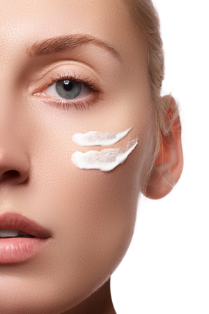 Beautiful face of young woman with cosmetic cream on a cheek. Skin care concept. Closeup portrait isolated on white. Close-up young beautiful face of girl applying moisturize cream.