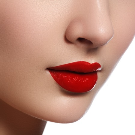 Close-up shot of woman lips with glossy red lipstick. Glamour red lips make-up, purity skin. Retro beauty style. Beautiful model girl with beauty makeup, red lips, perfect fresh skin. Youth and Skin Care Concept