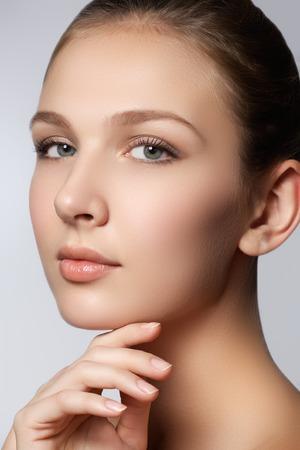 Femme de spa. Visage de beauté naturelle. Belle fille touchant son visage. Peau parfaite Soin de la peau. Jeune peau Ongles manucurés. Cosmétiques et maquillage