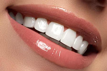 Macro happy woman's smile with healthy white teeth.Lips make-up. Stomatology and beauty care. Woman smiling with great teeth. Cheerful female smile with fresh clear skin Standard-Bild
