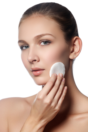 pleasantness: Happy european woman with cotton pad, isolated on white background. Beauty fresh girl cleaning face with cotton swab. Beautiful young woman cleaning her face with cotton