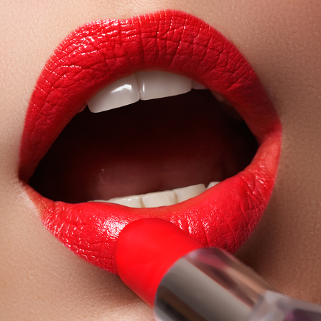 Woman applying lipstick. Model painted red lips. Beauty face with perfect fresh skin. Beauty concept