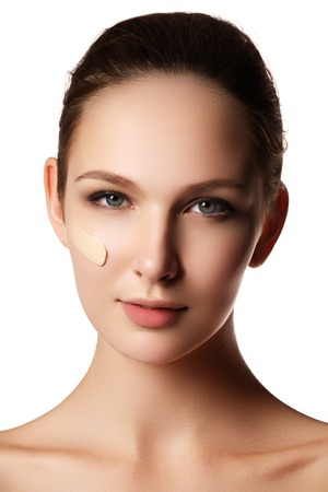 Beautiful face of young woman with cosmetic foundation on a skin. Beauty treatment concept. Makeup artist applying liquid tonal foundation on the face of the woman. Closeup photo of cheek Stock Photo