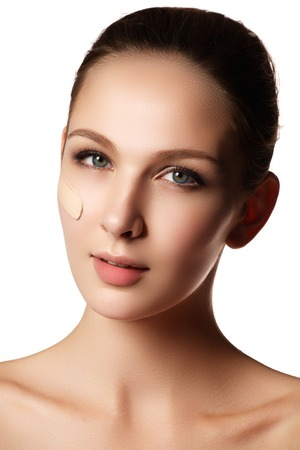 Make-up & cosmetics. Closeup portrait of beautiful woman model face with skin foundation on white background Stock Photo