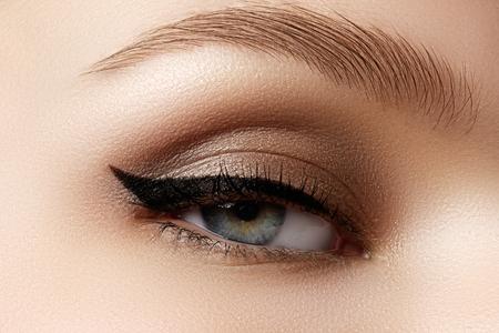 Cosméticos y maquillaje. Ojo femenino hermoso con maquillaje atractivo forro negro. Grande de la manera forma de flecha en el párpado de la mujer. Elegante maquillaje de la tarde