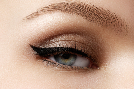Cosmetics & make-up. Beautiful female eye with sexy black liner makeup. Fashion big arrow shape on woman's eyelid. Chic evening make-up 免版税图像