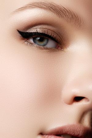 化粧品・ メイクアップ。セクシーな黒いライナー化粧品で美しい女性の目。女性のまぶたにファッションの大きな矢印図形です。シックな夜のメイ