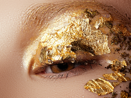 Cosmetics and make-up. Closeup macro shot of fashion sparcle visage. Closeup portrait of beautiful young woman with golden foil on face. Creative makeup. Stock Photo
