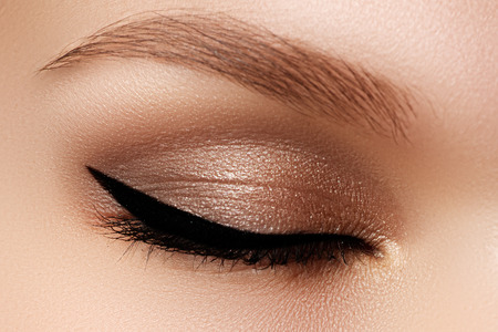 Cosmetics & make-up. Beautiful female eye with sexy black liner makeup. Fashion big arrow shape on woman's eyelid. Chic evening make-up 스톡 콘텐츠