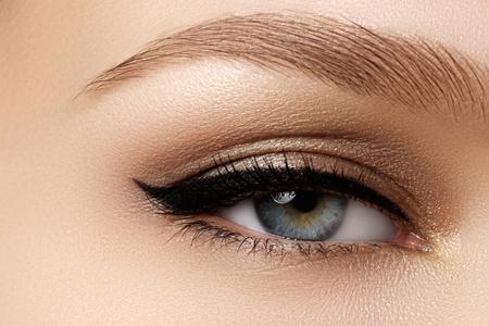 Cosmetici e make-up. Bella occhio femminile con il trucco sexy camicia nera. grande forma di freccia di modo sulla palpebra della donna. Chic trucco di sera