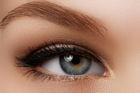 Cosmetics & make-up. Beautiful female eye with sexy black liner makeup. Fashion big arrow shape on woman's eyelid. Chic evening make-up Фото со стока