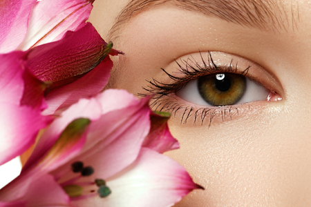 Gorgeous young model, beautiful woman eye with fresh pink  flower, part of female head, sexy girl with stylish look, spa and beauty background Stock Photo