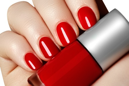 nailart: Manicure. Beautiful manicured womans hands with red nail polish. Bottle of nail polish.Trendy red nails