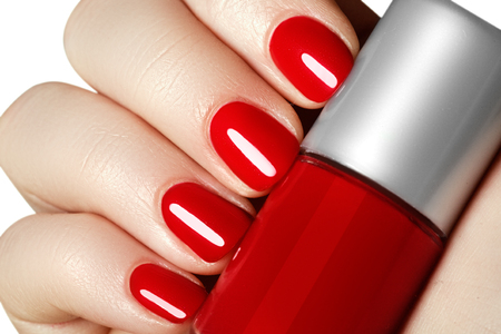 Manicure. Beautiful manicured womans hands with red nail polish. Bottle of nail polish.Trendy red nails