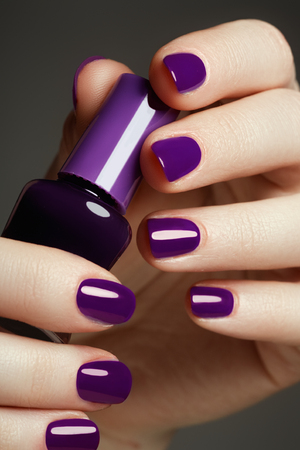 Bottle of nail polish. Beauty hands. Trendy stylish colorful nails, nailpolish. Great idea for the advertising of cosmetics. Beautiful manicuredl nails Stockfoto