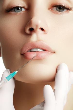 Porträt der jungen Frau, die kosmetische Injektion bekommen. Nahaufnahme der schönen Frau bekommt Injektion in ihrem Gesicht. Filler Injektionen. Lippenvergrößerung. Schöne perfekte Lippen