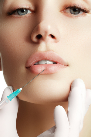 Portrait of young  woman getting cosmetic injection. Closeup of beautiful woman gets injection in her face. Filler injections.  Lip augmentation. Beautiful perfect lips