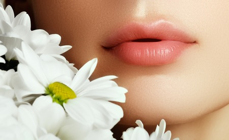 Lips with flower. Close-up beautiful female lips with bright lipgloss makeup. Perfect clean skin, light fresh lip make-up. Beautiful spa portrait with tender  flower. Spa and cosmetics Stock Photo